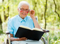 Lady in wheelchair reading bible with glasses sitting and the Royalty Free Stock Images