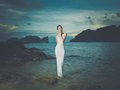 Lady in white dress on a seashore beautiful rocky shore Royalty Free Stock Images