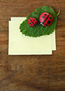 Ladybird and paper cobblestone on old wooden table Stock Photography
