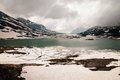Lago Bianco with snowy mountains and green water in lake, Bernina pass,Switzerland Royalty Free Stock Photo