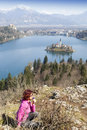 Lake bled and woman picking flowers beautiful panoramic view on famous cute brunette middle aged hiker smelling Stock Photo