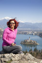 Lake bled and woman picking flowers beautiful panoramic view on famous cute brunette middle aged hiker smelling Stock Photos