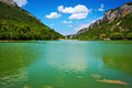 Lake and blue sky with clouds between the mountains there are some small remote people who relax on water in summer day Royalty Free Stock Photo