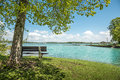 Lake chiemsee with tree and bench view to the on a day sun blue sky white clouds Stock Photography