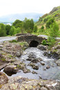 Lake district national park scenic view of old arched stone bridge over river in cumbria england Stock Photo