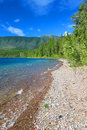 Lake mcdonald of glacier park small waves trickle through bright glacial rocks in national Stock Image