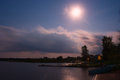 Lake night clouds moon landscape scape at the seliger russia by a summer sky with the forest at the opposite shore buildings and Stock Images
