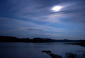 Lake night clouds moon landscape at the seliger russia by a summer sky with star trails the the forest at the opposite shore and Stock Photo