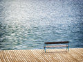 At the lake old wooden bench a Stock Photography