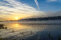 Lake sunrise fog sun mist colorful bright golden with on the with beautiful reflections of the clouds the and the trees in the Royalty Free Stock Photography