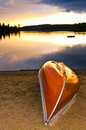 Lake sunset with canoe on beach Royalty Free Stock Images