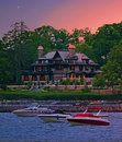 Lake at sunset with mansion and boats twilight Royalty Free Stock Image