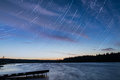 Lake sunset sky clouds tracks scenic orange and blue on the with falling stars in the form of shot on a long exposure Stock Photo