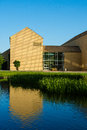 Lakeside theatre aarhus university denmark the giant yellow gable of the of is mirrored in the rippled lake on a summer evening Stock Image