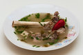 Lamb bone borsch on plate with red pepper and green fresh lovage Stock Image