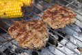 Lamb burgers sizzling minted on grill with corn cobs Stock Photography