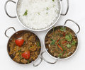 Lamb curries and rice from above a bowl of spiced curry with coriander leaves slivers of red green chillies next to a bowl of Stock Photos