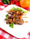 Lamb kebabs with yellow pepper and green salad on white plate close up Royalty Free Stock Images