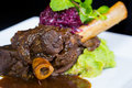 Lamb shank braised in an onion jus on white plate Royalty Free Stock Images