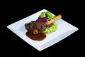 Lamb shank braised in an onion jus on white plate Stock Photography