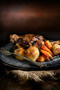 Lamb shank ii roast with roasted potatoes and carrots styled in a rustic setting with generous copy space concept image for home Stock Photography