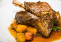 Lamb shank and potatoes a braised of in white plate with gravy Stock Photography