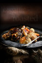 Lamb shank roast with roasted potatoes and carrots styled in a rustic setting with generous copy space concept image for home Royalty Free Stock Image