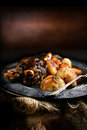 Lamb shank roast with roasted potatoes and carrots styled in a rustic setting with generous copy space concept image for home Stock Images