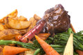 Lamb shank with vegetable in a rosemary and red wine jus on a white plate Stock Image