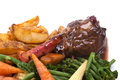 Lamb shank with vegetable in a rosemary and red wine jus on a white plate Royalty Free Stock Images