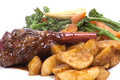 Lamb shank with vegetable in a rosemary and red wine jus on a white plate Royalty Free Stock Photos