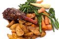 Lamb shank with vegetable in a rosemary and red wine jus on a white plate Stock Photo