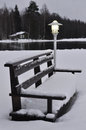 A lamp and a bench covered with snow Stock Images