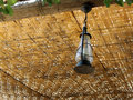 Lamp hanging from wicker roof a a ceiling made of Royalty Free Stock Image
