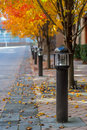 Lamp posts line a sidewalk with fall foliage lining suburban walkway parallel yellow and orange leaved trees Royalty Free Stock Photography
