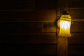 Lamp shade from illuminated vintage style lamp at the corner on wooden wall still life Royalty Free Stock Photography