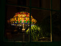 Lamp in window at night a stained glass tiffany style glowing a Stock Photography