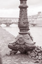 Lamppost base and the ponte vecchio bridge with river arno flor florence italy in black white sepia tone Royalty Free Stock Photography
