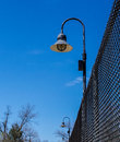 Lamps on chainlink fence a with attached against a blue sky Stock Photo