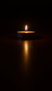 In a land of gloom a light has shone tealight candle on dark background Stock Image