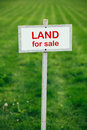 Land for sale sign against trimmed lawn background Royalty Free Stock Photo