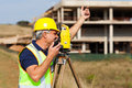 Land surveyor senior talking on walkie talkie at construction site Royalty Free Stock Photo
