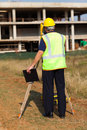 Land surveyor working rear view of senior at construction site with theodolite Royalty Free Stock Images