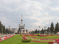 Landscape with flowers on the lawn moscow september palace and red a green and people walking in park at exhibition centre in Royalty Free Stock Photos