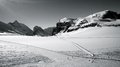 Landscape of mountain alps with skiers and their tracks Royalty Free Stock Images