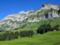 Landscape of mountain massif the monumental a with a chalet at the summit and lush meadows with small forests beneath summer in Royalty Free Stock Images