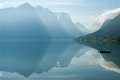 Landscape with mountains reflecting in the lake and small boat, Norway Royalty Free Stock Photo