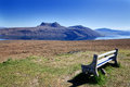 Landscape of the northern scotland wooden bench with beautiful view to the calmness lake and mountains Royalty Free Stock Images