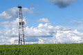 Landscape with oil drilling rig blue sky and green wheat Royalty Free Stock Image