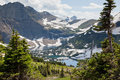 Landscape rugged mountains patches snow melting hidden lake valley framed evergreen trees glacier national park montana Stock Images